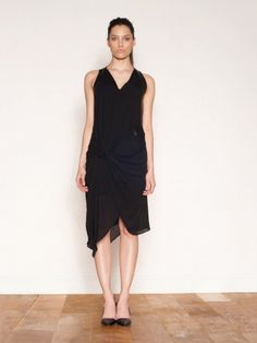 Helmut Lang Leather Paneled Lush Dress. A modern twist on the classic black dress, the leather inserts add dimension and texture to this perfect, timeless addition to your wardrobe. The shape of the dress lends itself to the female form using key Lang drapery and layering - optimized by a twist detail which sits at the hip. The wrap V-neckline falls to the antisymmetric hem which sits just below the knee on the shortest side. The dress is fully lined with a silver zip fastening at the back.