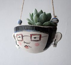Ceramic Hanging Head- Iris A hand formed stoneware planter with hand painted character. Has little earrings and handmade ceramic bead decoration. Hung on a length of cotton cord. Lips and glasses frames have transparent glaze on them for a glossy look.