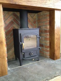 Clearview Pioneer 400, chunky solid oak surround, reclaimed Yorkshire stone hearth, herringbone brick to rear and standard brick work to sides.