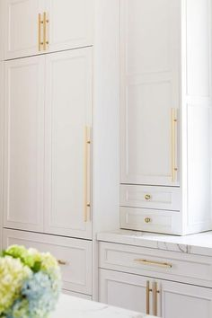 White cabinets adorned with long brass pulls and brass knobs paired with Silestone quartz countertops. White cabinets adorned with long brass pulls and brass knobs paired with Silestone quartz countertops. White Shaker Cabinets, White Kitchen Cabinets, Kitchen White, Gold Kitchen Hardware, Country Kitchen, Gold Cabinet Hardware, Wall Cabinets, Grey Cabinets, Cupboards