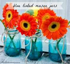 Blue tinted mason jars filled with a bright flower are sure to bring spring to your porch - ItAllStartedWithPaint.com