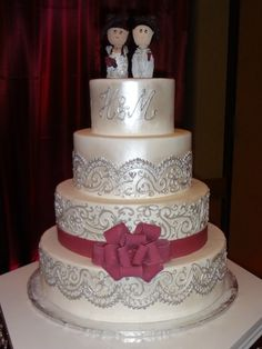 Pearl and silver lace wedding cake with burgundy bow