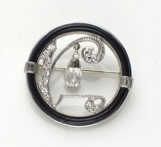An art deco diamond, black onyx and platinum brooch the platinum circle brooch depicting a stylized tree set with single-cut diamonds, suspending a diamond briolette drop, the black onyx frame accented by baguette-cut diamonds, completed by a gold pin back.