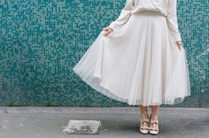 pleated skirt + teal wall
