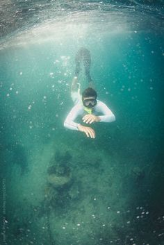 Snorkeler diving under the sea by Jovana Milanko
