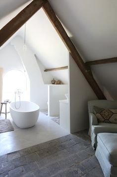 Brilliant Bathroom mixing honed blue limestone floor and exposed timber roof truss.  Simple white fittings and linen to soften.