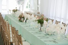 Mint green wedding tablescape with mint linens, pink rose centerpieces,  ivory napkins, and gold chivari chairs. Photography by Susie