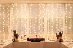 Lights behind sheer fabric behind the bridal table