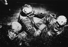 Photographer/Creator  Gary Settle  Collection  1965  Publisher  Topeka Capital-Journal  Caption/Description  Three football players landing with a splash in the mud.