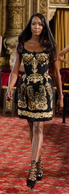 Naomi Campbell in a regal brocade Dolce & Gabbana top, bodysuit and skirt ensemble, with killer Alexander McQueen strap-up wedges.