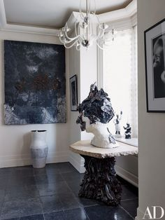 In the powder room are a Gio Ponti chandelier, a Kiefer painting, and a bust by Klara Kristalova