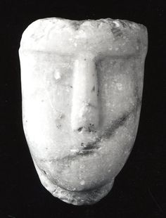 sculpture; Ancient South Arabian; 3rdC BC-3rdC; Yemen; Yemen. Very crude, carved calcite-alabaster human face with very angular features; no eye sockets; only mouth, nose and eyebrow ridge; topped off at hairline; incomplete?; possibly from a larger object.