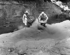 1948 American-Australian Scientific Expedition to Arnhem Land - Fred McCarthy and Frank M Setzler shovelling and sifting cave deposits in front of picture gallery, Gunbalanya, October 1948.