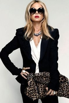 Rachel Zoe wearing flowy white blouse, black blazer, blingy necklace, and animal print
