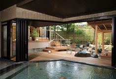 Indoor Japanese pool and accompanying outdoor deck with  a calming arrangement. -  たちばな四季亭、加賀山代温泉、石川