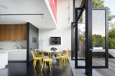 Love the stark contrast of the yellow dining chairs against the black and white of the interior.