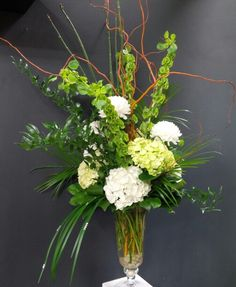 Floral design by Lilies White. Hydrangea, bells of ireland, chrysanthemums, roses and curly willow.