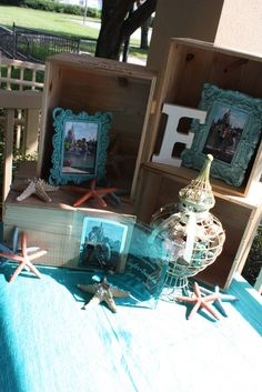 Welcome Table - pics of Jeff and Karen inside wooden crate boxes in colorful frames with shells.. starfish, etc...