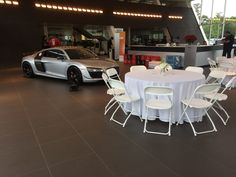 White Hercules chairs and round tables at the Jim Ellis Audi Atlanta showroom. The Audi doesn't hurt the decor of the room either. Corporate Event Planner, Corporate Events, Table Linen Rentals, Johns Creek, Round Tables, Hercules, Audi R8, Showroom, Atlanta