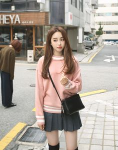 Large pink sweater, gray pleated skirt, black purse, black above-the-knee socks