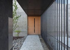 Via thehardt The entrance to the JuuL House (2012) by NKS Architects located in Yukuhashi, Fukuoka, Japan. The 4,434 ft² (412 m²) home sits adjacent to a river running through the suburbs of a small city in Fukuoka Prefecture. The client, a musician involved with music education in the local community, wanted a home that could also function as a small music hall. Because the client works in the cement business – a major regional industry – the architects used concrete as the primary…