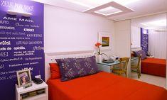 Bem personalizadoA cor base deste quarto projetado pelo escritório Arqluz é neutra e permitiu ousar nos demais elementos da decoração. O vermelho vibrante da colcha conversa com o roxo do papel de parede, dando vida ao espaço. A iluminação indireta destaca alguns pontos do quarto, como a frase na parede.