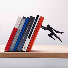 "'Book & Hero' by Artori Design is a new product to join Artori Design's series of black metal accessories for holding ""falling books"". Books lean on it at a special angle, opposite to the 'Falling bookend'. A superhero character seems to hold the books preventing them from falling. An uncommon bookshelf that book lovers and super heroes fans can't remain indifferent to… and a great conversation starter as well. Made of metal. 20 x 12 x 17 cm."