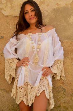 Sexy y fresco vestido estilo ibicenco en puro algodon. Mangas francesas, escote bote elastizado con bordados. Bajo irregular y bajo de mangas con puntilla realizada a mano al crochet. Talla Unica