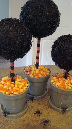 Spider topiary for Halloween. foam ball painted black, glue on spiders, paint stick in halloween colors, candy, florist foam in pots