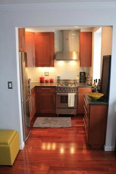 warm wood [cherry?] cabinets, stainless steel appliances and hardware. i think this look works here because the cabinets 'match' the floor.