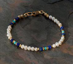 Esta delicada pulsera de perlas características pequeñas (3-4mm) de perlas blancas cultivadas redondeos, con buen brillo, acentuado con genuino azul lapislázuli auténtico dormir belleza turquesa cuentas. El blues se fijan apagado de uno a y de las perlas por los granos de pirita de oro facetado espaciador. Se trata de un hermoso aspecto clásico en un elegante delicado tamaño. La pulsera se cierra con un broche de langosta lleno oro de 14K que sujeta a un gran anillo de oro llenado cierre…