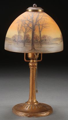 HANDEL ENAMELED GLASS BOUDOIR LAMP, EARLY 20TH CENTURY. The acid etched mushroom dome shade enameled with a twilight winter scene of barren trees. Raised on a patinated metal base.