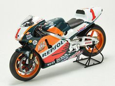 This Honda NSR500 (Mick Doohan - 1998) Diecast Model Motorcycle is Red and Orange and features working stand, steering, wheels. It is made by Ex Mag and is 1:12 scale (approx. 17cm / 6.7in long).    Please note: imperfect outer packaging on this item....