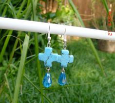 These are light weight turquoise cross earrings with medium blue crystal accent.  They are on Fish hook earrings.