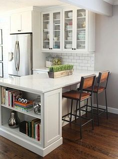 subway tile, white cabinets with glass doors stainless refrigerator, bar stools, wood floors