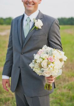 sweet photo of the groom holding the bride's bouquet - and what a pretty bouquet! photo by @Christa Elyce