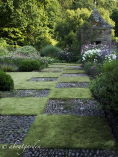 Patchwork Garden - stone mosaic squares and grass and a beautiful flower garden border.