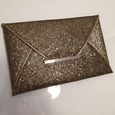 "Gold Glitter Envelope Clutch A glittered envelope clutch featuring a mesh overlay. High polish hardware. Metallic faux leather trim. Two interior pockets. Fully lined. Lightweight. Great for the holidays!  7.25"" H x 11.25"" W x 0.5"" D Shell: 100% PU; Lining: 100% polyester NWT ❌No trades Bags"