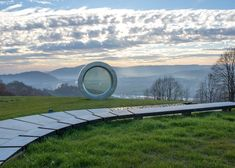 """Giant Fractured Camera Lens Sculpture Pays Tribute to a Fallen Photographer. """"Sitting atop Cukur hill in Banovina, Croatia is a sculpture of a giant camera lens. Its clean, circular form is nearly flawless, but it has one subtle imperfection—there is a single bullet hole that fractures the crystal-clear glass. This crack is intentional, and its significance honors a fallen Croatian photographer named Gordan Lederer who lost his life in 1991."""