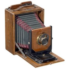 "Polished Wood Folding Camera by Möller, Wedel, c. 1890 J.D. Möller (Wedel in Holstein), producer of the world-famous ""Cambinox"" camera. – Plate size 3 ½ x 4 3/4 in., polished wood, green bellows with dark-red corners, brass lens with rotating stop, with wooden double cassette. Provenance: J.D. Möller museum in Hamburg (until the 1980's) – Not mentioned in any literature."