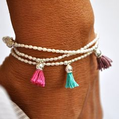 A delicate and feminine bracelet with a spot of color. Stunner! This lovely bracelet is made of tiny oval fresh water pearls with sterling silver beads and a silk tassel to give it a little spot of co