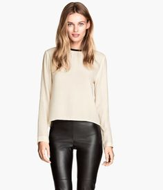 Straight-cut blouse in woven fabric with long sleeves. Cut-out section at back of neck with snap fastener closure. Rounded hem, slightly longer at back.