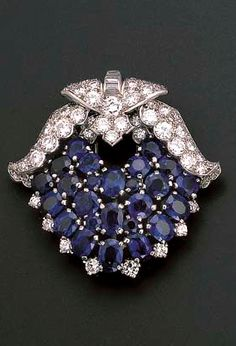 AN ART DECO SAPPHIRE AND DIAMOND CLIP BROOCH, BY CARTIER  Designed as a triple-row of cushion-cut sapphires with baguette-cut and pavé-set diamond winged surmount, circa 1930