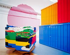 """Jessica Stockholder, """"Vortex in the Play of Theatre with Real Passion,"""" 2000. Duplo, theatre curtain, work site containers, bench, theatre light, linoleum, tables, fur, newspaper, fabric, and paint."""