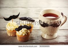 Delicious creative cupcakes and cup of tea on wooden table