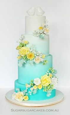 Ombre wedding cake in white and teal with yellow and white flowers, only need two tiers