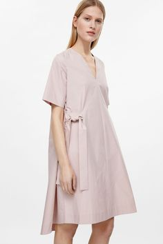 Coming in at the waist, this v-neck dress has tie belts on either sides, creating a deep pleated effect. Made from smooth cotton, it is completed with in-seam pockets, a graduated, rounded hemline and short sleeves.