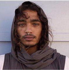 Dark man, nose pierce, big thick eyebrows, curly long hair, light brown eyes, and beard