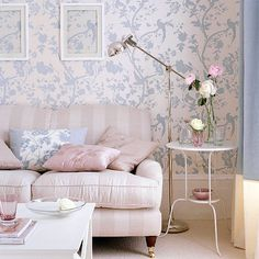 Pink sofa in front of blue and white printed wallpaper