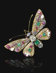 FORMERLY IN THE COLLECTION OF DON JOSÉ MARÍA DE MARTORELL Y TÉLLEZ GIRÓN, XVIII DUQUE DE PLASENCIA AND HIS WIFE DOÑA MARIA DE LA CONCEPCIÓN. Gem set and diamond brooch, circa 1900. Designed as a butterfly, the head and thorax set with a step-cut sapphire and emerald, and an oval and pear-shaped diamond, the wings set with variously shaped rubies, opals, emeralds and diamonds.